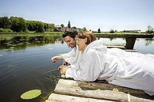 Paar liegt auf Holzsteg über dem Wasser