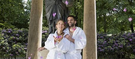 Paar im Bademantel steht im Blütenregen