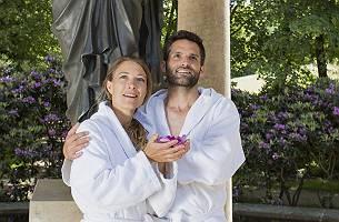 Paar im Bademantel steht vor antiker Statue