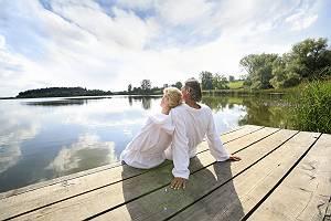 Paar im Bademantle genießt die Sonne auf einem Steg im See
