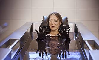 Frau in Moorbad ihre mit Moor bedeckten Hände betrachtend