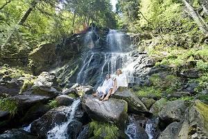 Paar im Bademantel entspannt sich am Wasserfall