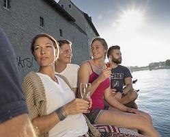 4 Freunde genießen bei einem Glas Sekt den Feierabend an der Do