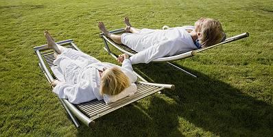 Paar im Bademantel sonnenbadet im Garten