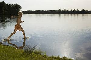Junge rennt ins Wasser eines Sees