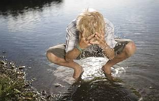 Blonder Junge erfrischt sich am See