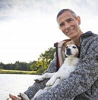 Tierhalter hält alten Hund beschützend auf dem Arm