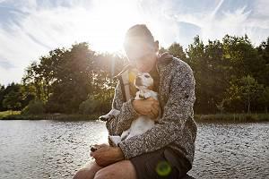 Mann liebkost seinen Hund am Wasser sitzend