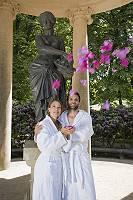 Paar im Bademantel steht vor antiker Statue im Blütenregen