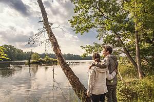 Junges Paar genießt den abendlichen Ausblick auf einen See