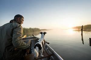 Mann mit seinem Hund auf einem Bootsausflug am Federsee