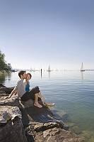 Sportliches Paar entspannt gemeinsam am Bodensee