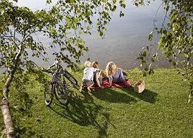 Freundinnen mit Sohn rastet nach Radtour am Seeufer