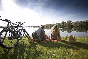 Freundinnen genießen mit Sohn nach Radtour den Blick über eine