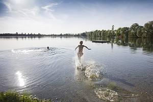 Junge rennt spritzend ins Wasser eines Sees