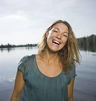 Junge Frau, eine natürliche Schönheit, herzlich lachend steht