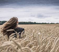 Junge Frau mit langem wehendem Haar genießt den Wind in einem G