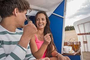 Paar spielt Schere, Stein, Papier im Strandkorb