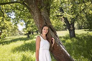 Portrait einer Frau im weißen Kleid auf einer Obstwiese