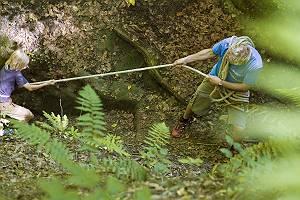Vater zieht Sohn mit einem Seil einen steilen Weg hinauf, erstes