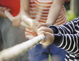 Kinder ziehen gemeinsam an einem Seil