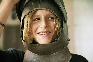 Jungen erprobt mit Ritterhelm auf dem Kopf wie es sich anfühlt