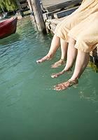 Zwei Personen hängen ihre Füße ins Wasser