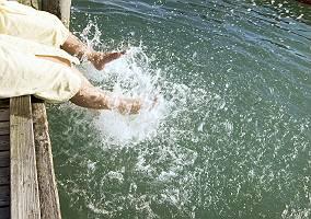 Zwei Personen spritzen Wasser mit ihren Füßen
