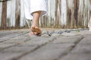 Eine Frau in weißer Hose erlebt einen Barfußpfad