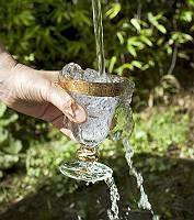 Ein Glaskelch mit Goldrand wird an einer Quelle gefüllt