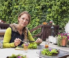 Frau isst Salat auf Terrasse