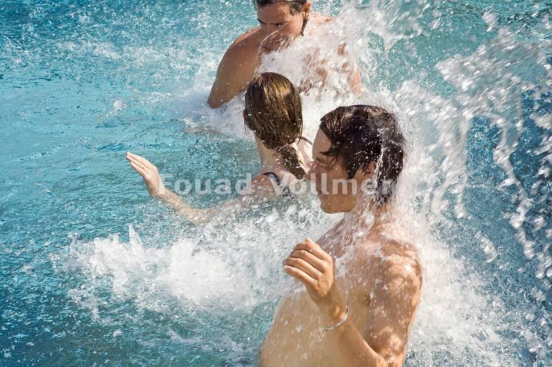 Drei Personen genießen eine anregende Wassermassage im Pool
