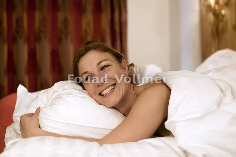 Frau erwacht glücklich aus dem erholsamen Schlaf