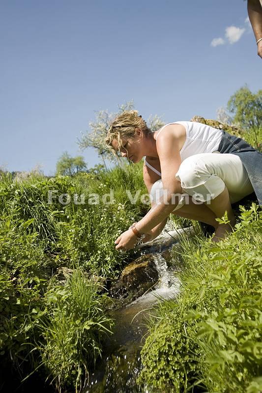Frau sitz in der Hocke an einem kühlen kleinen Bach im Sommerun