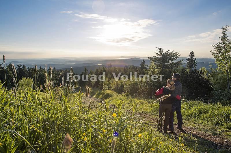 Paar steht Arm in Arm auf dem Fichtelberg und blickt auf das Ber