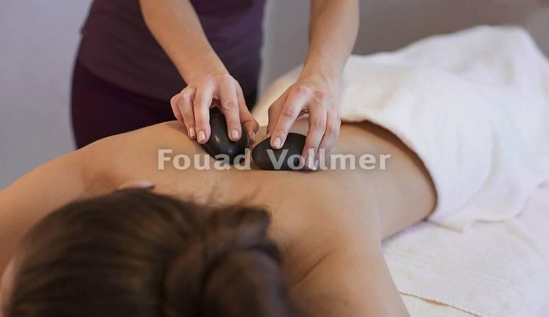 Rückenmassage Hot Stone an einer jungen Frau im Spa