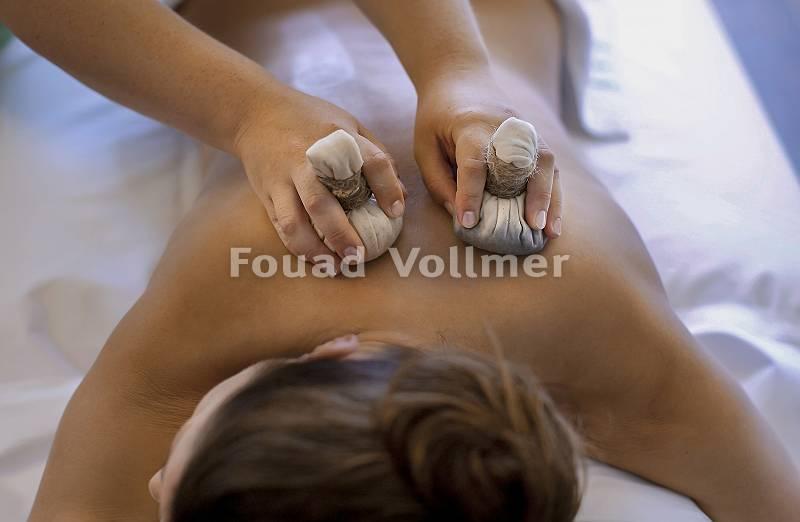 Kräuterstempelmassage an einer jungen Frau mit Leinensäckchen