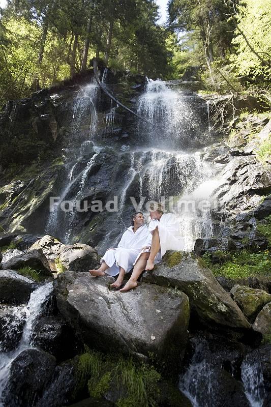 Paar sitz im Bademantel auf einem Felsen direkt vor einem Wasser