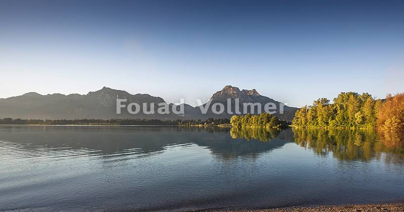 Blick über den Forggensee auf ganz klein das Schloss Neuschwans