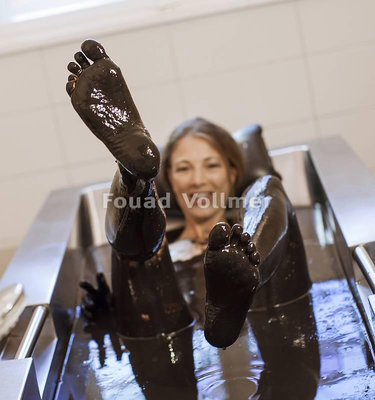 Frau, die in einem Moorbad ihre Beine in die Luft streckt