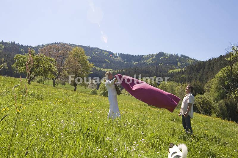Paar breitet Decke für Picknick aus