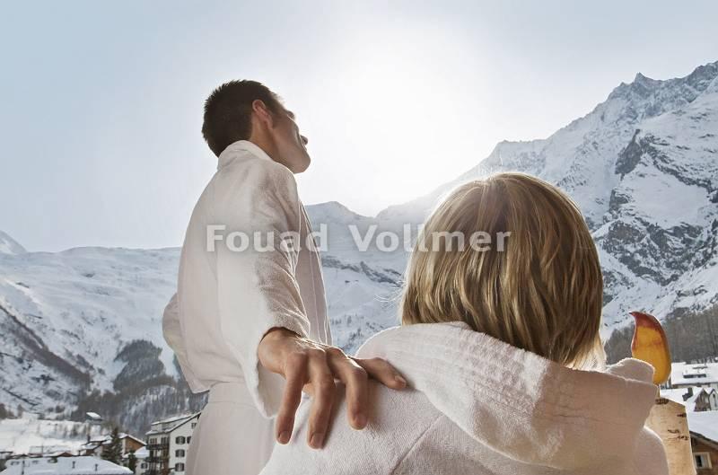 Paar im Bademantel mit verschneitem Alpenblick