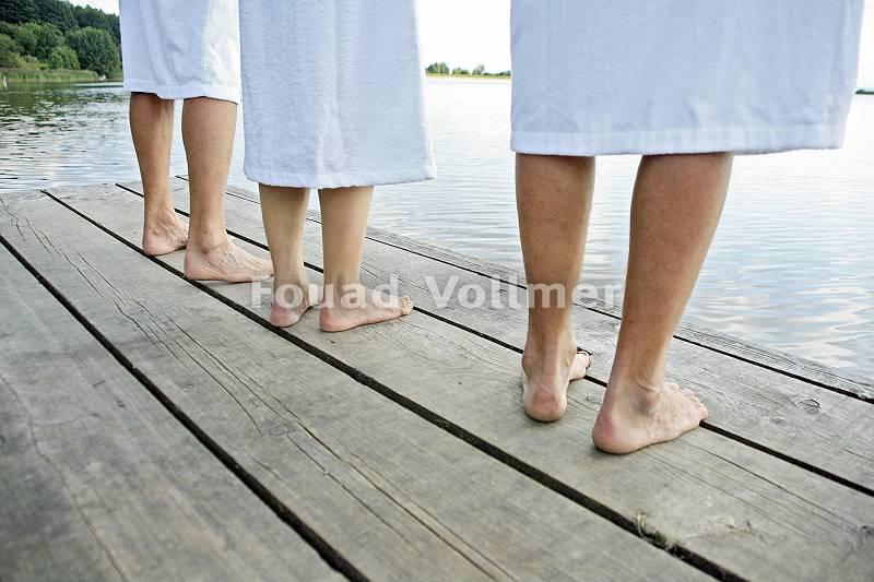 Füße auf Holzsteg am See