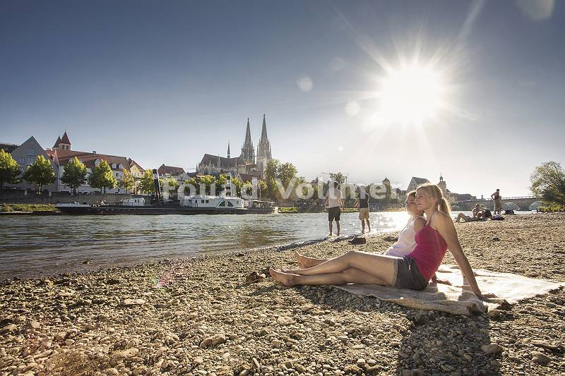 Junge Leute entspannen an der Donau mit Blick auf den Dom in Reg