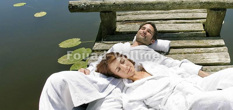 Paar im Bademantel genießt die Sonne auf einem Steg am See
