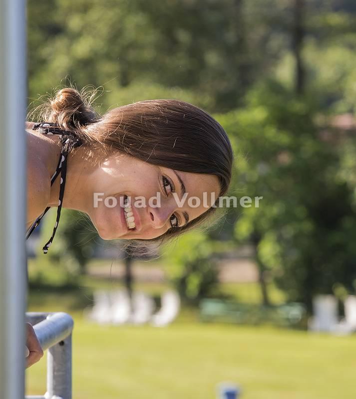 Junge strahlende Frau beugt sich verschmitzt über Geländer