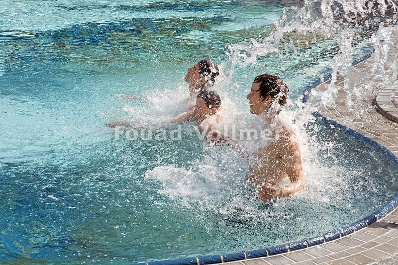 Drei Männer genießen eine anregende Wassermassage