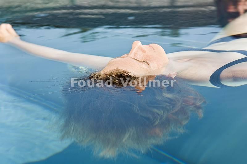 Frau lässt sich im Pool an der Wasseroberfläche treiben