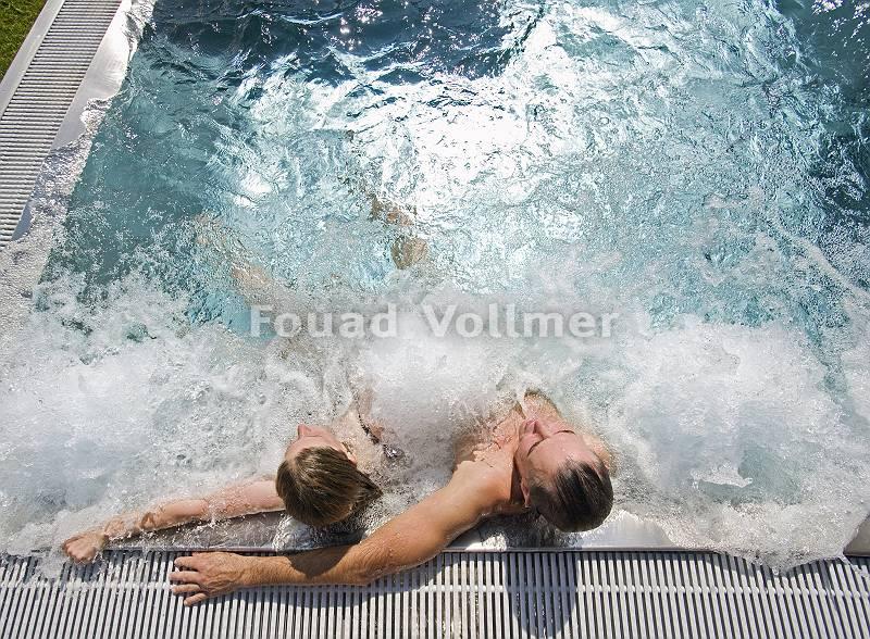 Paar genießt die Sonne auf Wassermassageliegen im Pool