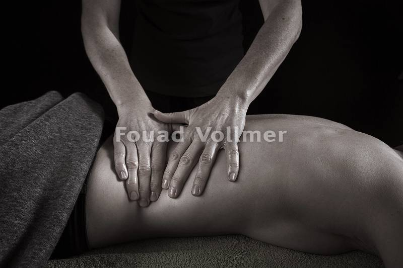 Masseur knetet Rücken während Rückenmassage